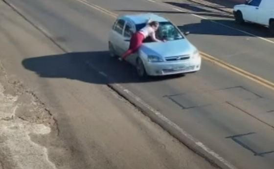 Câmeras flagram mulher sendo transportada em capô de veículo no Paraná